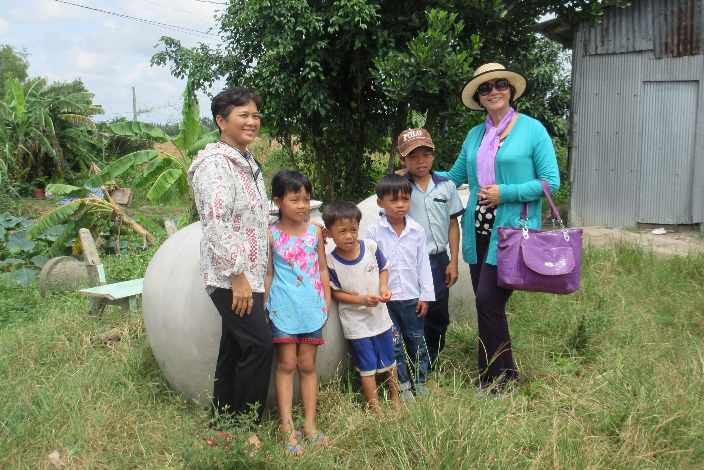 Delighted villagers with their new rain water vat